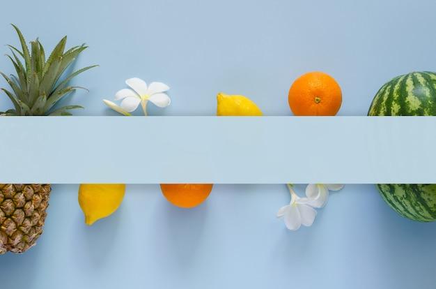 パイナップル、レモン、オレンジ、スイカ、フランジパニの花と青い背景のテキストの空白スペースと夏の背景の概念