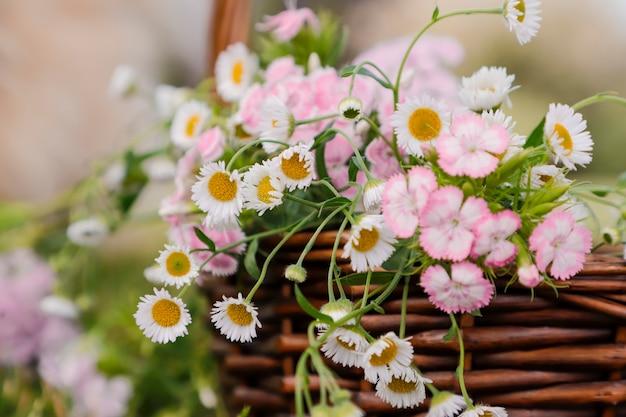 Summer background fragment of summer flowers bouqet gelichrysum and garden cloves in a basket