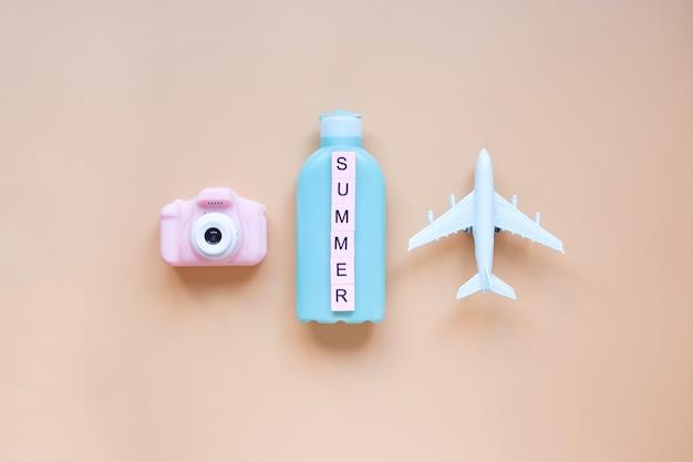 夏の背景モデル飛行機ピンクのカメラと日焼け止めクリームのボトル休暇と旅行