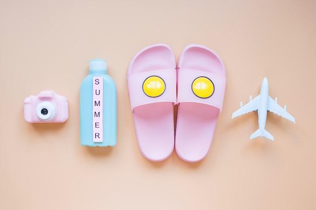 夏の背景モデル飛行機ピンクカメラビーチスリッパと日焼け止めクリーム