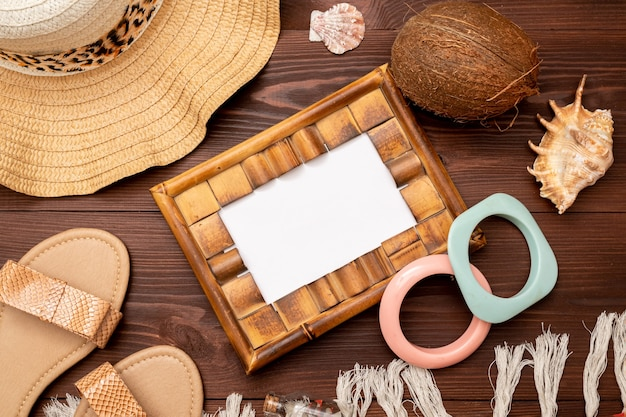 여성용 샌들, 사진 프레임, 밀짚 가방, 나무 표면에 밀짚 모자의 여름 배경