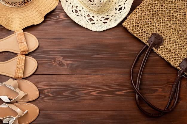 여성용 샌들, 밀짚 가방, 나무 표면에 밀짚 모자의 여름 배경