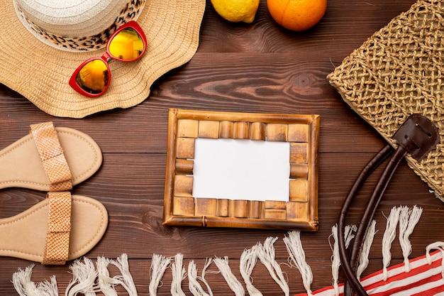 여성용 샌들, 밀짚 가방, 밀짚 모자, 사진 프레임, 나무 표면에 있는 파레오의 여름 배경