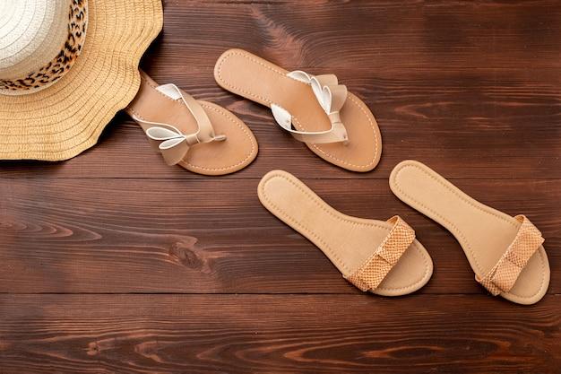 여성용 샌들의 여름 배경, 나무 표면에 밀짚 모자