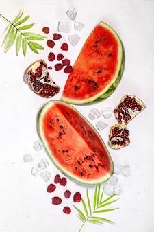 夏の背景:ザクロの果実、ラズベリー、氷、白い背景の上のヤシの葉、フラットレイ、上面図と新鮮なスイカのスライス。