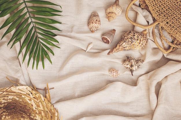 Летний фон соломенная шляпа сумка с морскими ракушками пальмовый лист на текстильном льняном фоне