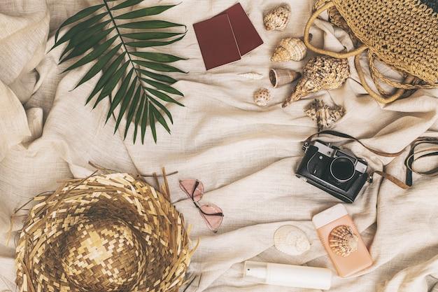 Летний фон соломенная шляпа сумка с ракушками розовые очки косметика паспорта фотоаппарат пальмовый лист на текстильном льняном фоне