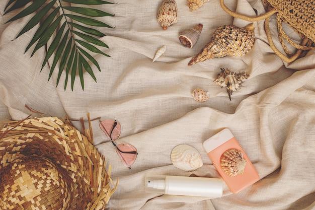 Летний фон соломенная шляпа сумка с ракушками розовые очки защита от солнца пальмовый лист на текстильном льняном фоне