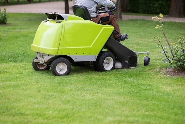 Летний фон с езда ландшафтным дизайнером на лужайке, косящей траву