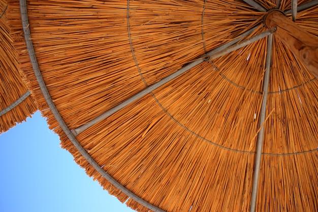 青い空と太陽の傘と夏の背景。
