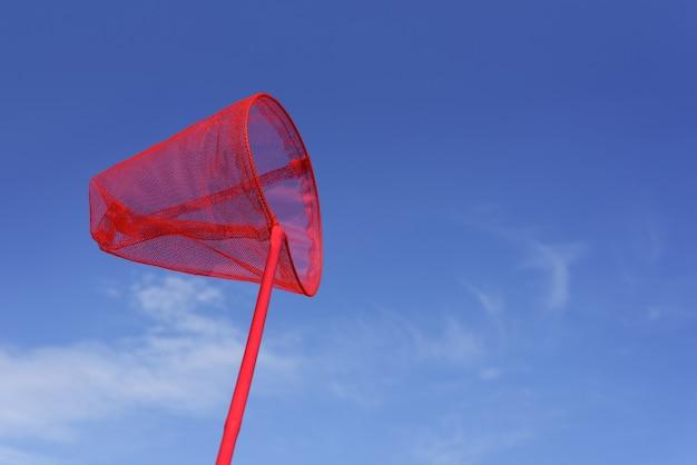 Летний фон с ярким объектом. красный сачок для ловли бабочек или рыбок. детские забавы