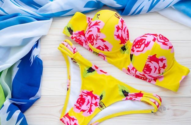 夏の背景にファッションビーチウェア、黄色のビキニ、木製の背景に青いパレオ