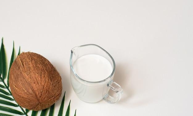 Летний фон с пальмовым листом, кокосом и веганским органическим кокосовым молоком в стеклянном кувшине