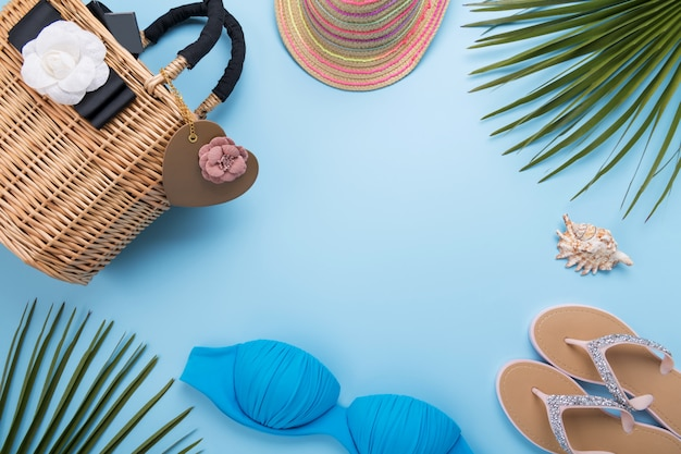 Summer background with palm leaves, fashion hat, bikini, flip flops, straw beach bag on a light pastel blue background, travel and vacations concept, top view