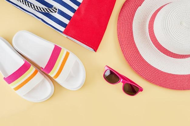 わらのビーチ帽子、サングラス、バッグ、ビーチサンダルと夏の背景。夏の旅行のコンセプト。