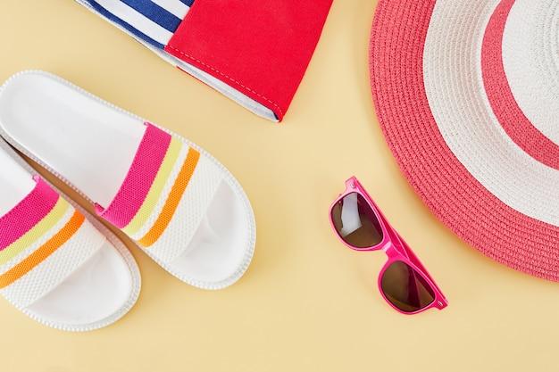 わらのビーチ帽子、サングラス、バッグ、ビーチサンダルで夏の背景。夏の旅行のコンセプト。