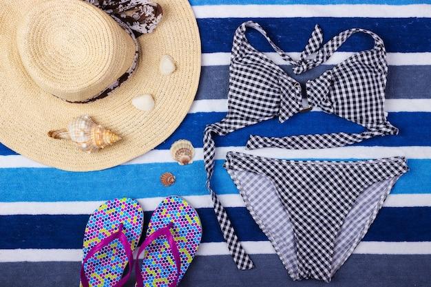 麦わら帽子、ビーチサンダル、水着と夏の背景。上面図