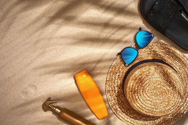 Summer background with straw hat sunglasses sunscreen bottle and flip flops