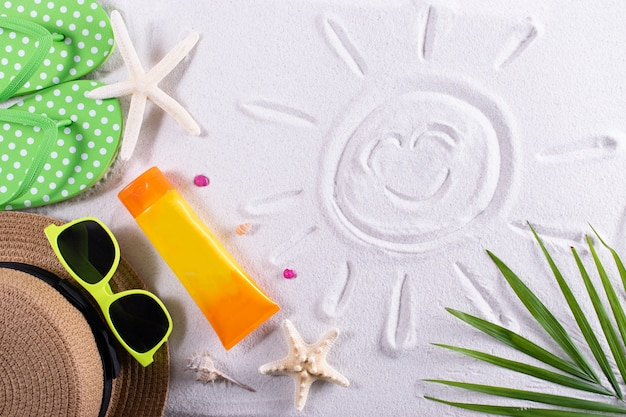 Summer background with sunglasses, hat and flip flops on sand background. holiday vacation concept.