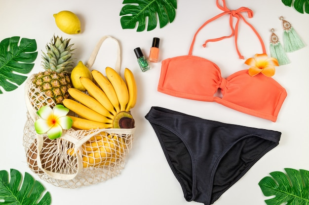 Summer background woman's beach accessories swimsuit, tropical fruits in eco bag, palm leaves on white