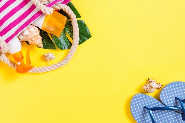 コピースペースを持つ夏のバッグの背景。フラットは、カラーテーブル、旅行の概念に写真を置きます。テキスト用の空き容量