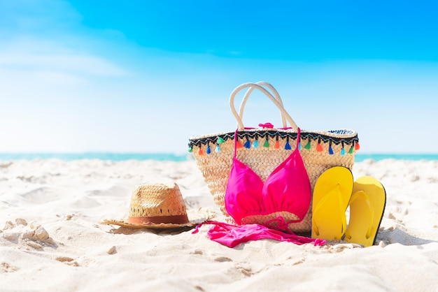 Summer bag, slipper, hat and bikini on the tropical beach with blue sky background.