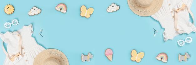 Летний баннер с белым платьем, соломенной шляпой, солнцезащитными очками и забавными пряниками на синем фоне. концепция lookbook девушки моды. вид сверху плоская планировка копирование пространства.