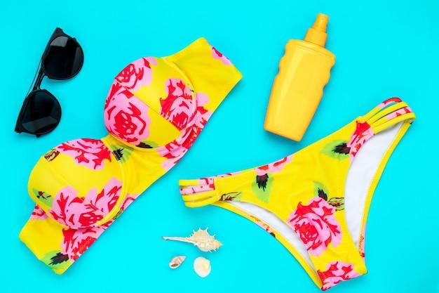 Летние пляжные аксессуары на синем фоне. модная пляжная одежда, желтое бикини. купальник с цветочным принтом. купальник женский. концепция морского отдыха, досуга.