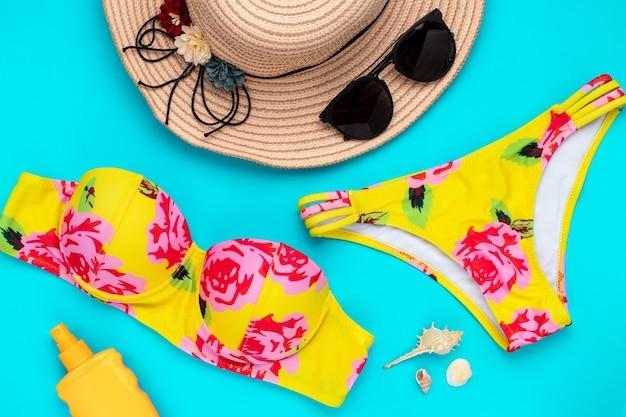 Летние пляжные аксессуары на синем фоне. модная пляжная одежда, желтое бикини. концепция морского отдыха, досуга. купальник с цветочным принтом. купальник женский.