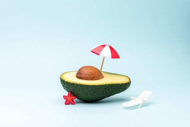 Летний пляжный фон из фруктов авокадо, зонтик от солнца и шезлонг