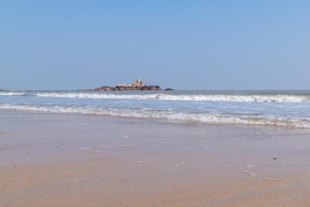 Летний пляж, голубое небо, золотой пляж и небольшие волны