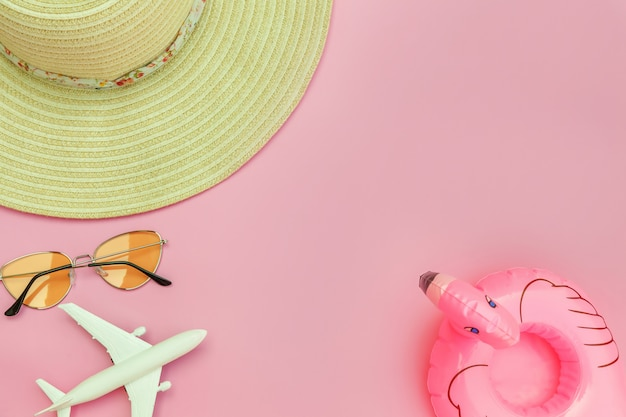 Summer beach composition. minimal simple flat lay with plane sunglasses hat and inflatable flamingo isolated on pastel pink background. vacation travel adventure trip concept. top view copy space.