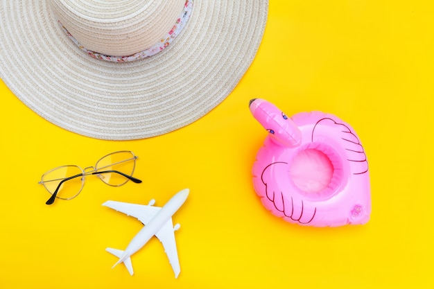 Summer beach composition. minimal simple flat lay with plane sunglasses hat and inflatable flamingo isolated on yellow background. vacation travel adventure trip concept. top view copy space.