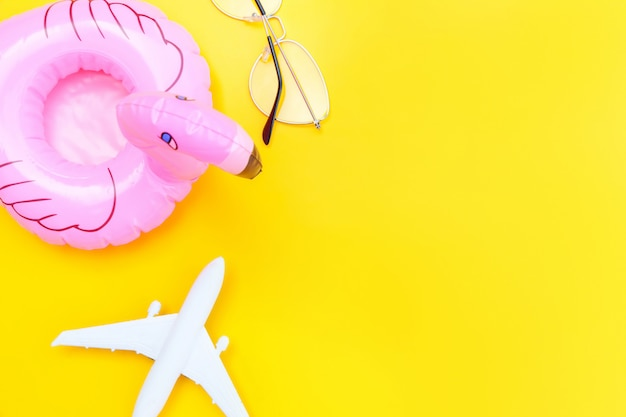 Summer beach composition. minimal simple flat lay with plane sunglasses and inflatable flamingo isolated on yellow background. vacation travel adventure trip concept. top view copy space.