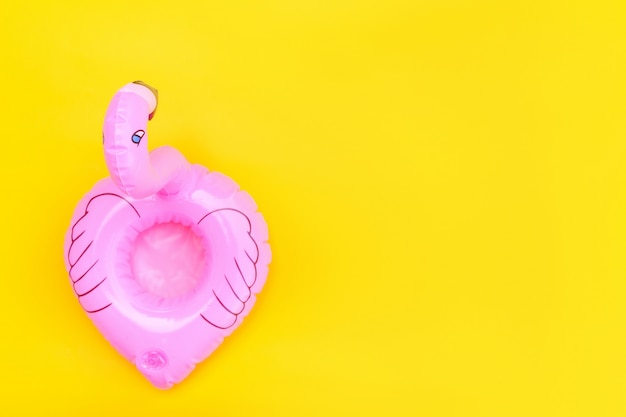 Summer beach composition. simply minimal design with pink inflatable flamingo isolated on yellow background. pool float party, trendy celebrity fashion concept. flat lay top view copy space.