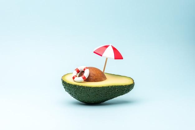 Концепция летнего пляжа с зонтиком от солнца и плавательным кольцом из фруктов авокадо