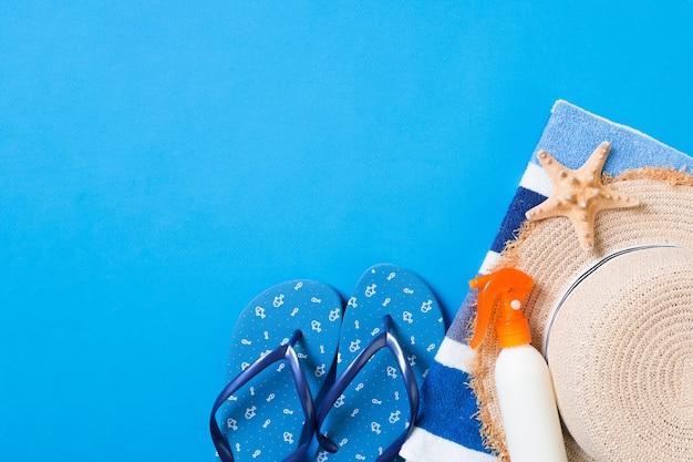 夏のビーチフラットレイアクセサリー。日焼け止めボトルクリーム、麦わら帽子、ビーチサンダル、タオル、貝殻の色付きの背景。コピースペースで旅行休暇のコンセプト。