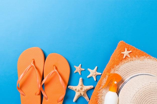 Летние пляжные аксессуары для квартиры. крем для солнцезащитных бутылок, соломенная шляпа, шлепки, полотенце и ракушки на цветном фоне. концепция праздника путешествия с копией пространства.