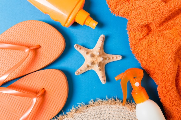 Summer beach flat lay accessories. sunscreen bottle cream, straw hat, flip flops, towel and seashells on colored background. travel holiday concept with copy space.