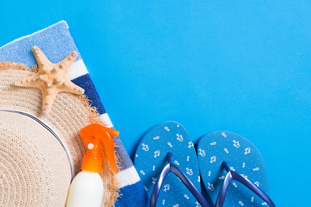 Summer beach flat lay accessories. sunscreen bottle cream, straw hat, flip flops, towel and seashells on colored background. travel holiday concept with copy space