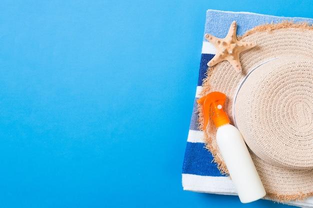 夏のビーチフラットレイアクセサリー。色付きの背景に日焼け止めボトルクリーム、麦わら帽子、タオル、貝殻。コピースペースで旅行休暇のコンセプト。