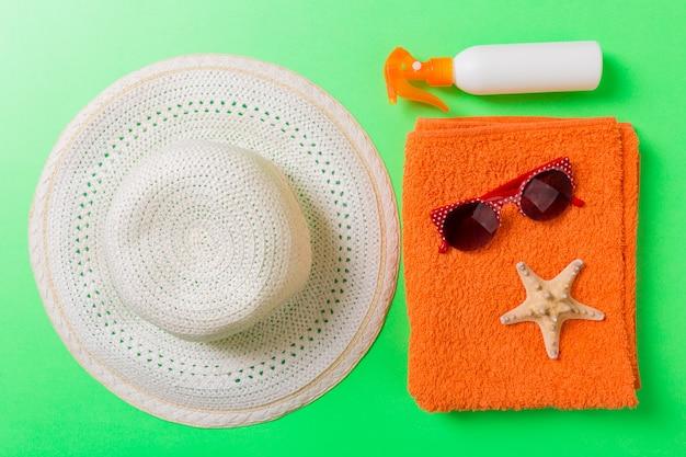 夏のビーチフラットレイアクセサリー。色付きの背景に日焼け止めボトルクリーム、タオル、貝殻。コピースペースで旅行休暇のコンセプト。
