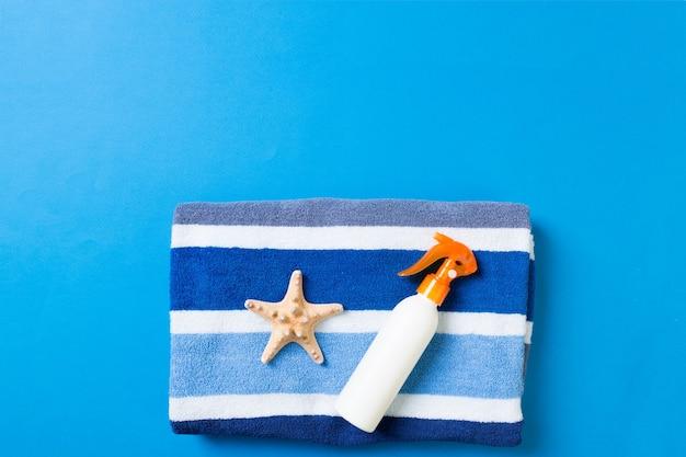 Летние пляжные аксессуары для квартиры. крем бутылки солнцезащитный крем, полотенце и ракушки на цветном фоне. концепция праздника путешествия с копией пространства.
