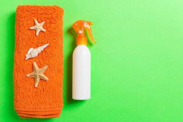 Летний пляж с плоскими прокладками. солнцезащитный крем бутылка крем, полотенце и ракушек на цветном фоне. концепция путешествия праздник с копией пространства