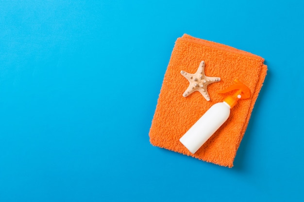 Summer beach flat lay accessories. sunscreen bottle cream, towel and seashells on colored background. travel holiday concept with copy space.