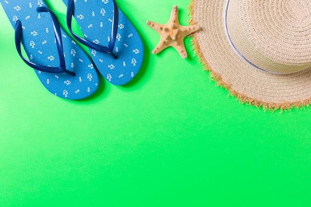 夏のビーチフラットレイアクセサリー。色付きの背景に日焼け止め麦わら帽子、ビーチサンダル、貝殻。コピースペースで旅行休暇のコンセプト。