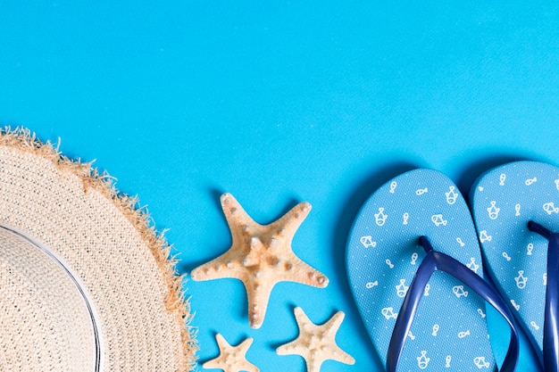Summer beach flat lay accessories. sunscreen straw hat, flip flops and seashells on colored background.