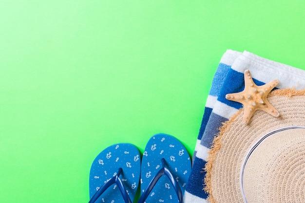 夏のビーチフラットレイアクセサリー。色付きの背景に日焼け止め麦わら帽子、ビーチサンダル、タオル、貝殻。コピースペースで旅行休暇のコンセプト。