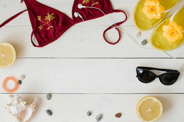 Summer beach flat lay, yellow flip-flops, burgundy swimsuit, headphones, sunglasses, sea pebbles and seashell