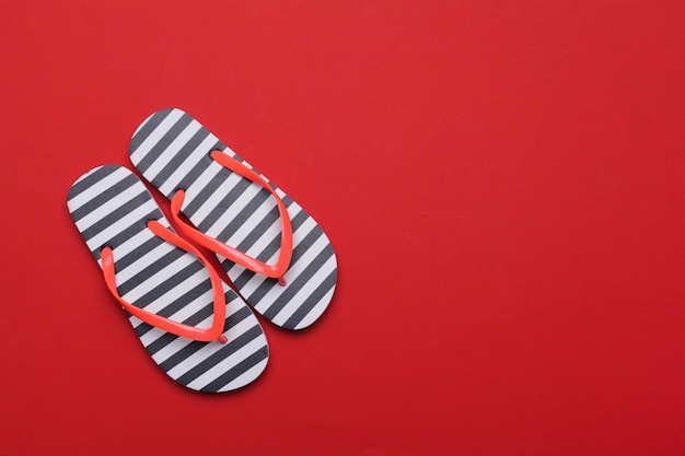 Summer beach flip flops on red